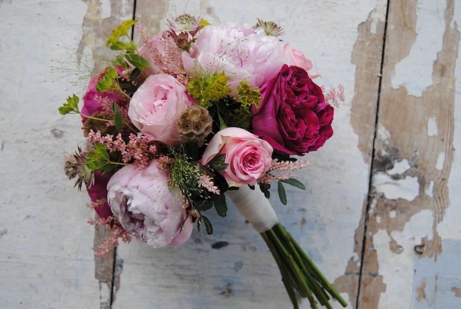 Ramo de novia con rosas David Austin y peonias en tonos rosa, fucsia y verde claro.